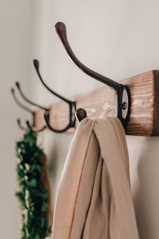 Entryway with a diy farmhouse coat rack. There is a wreath and shawl hanging from the coat rack.