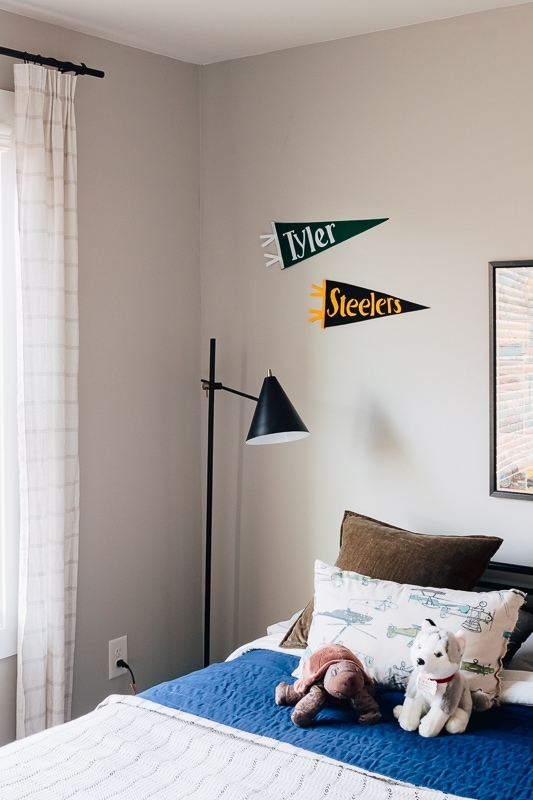 two personalized diy felt pennants hanging on the wall in a bedroom.