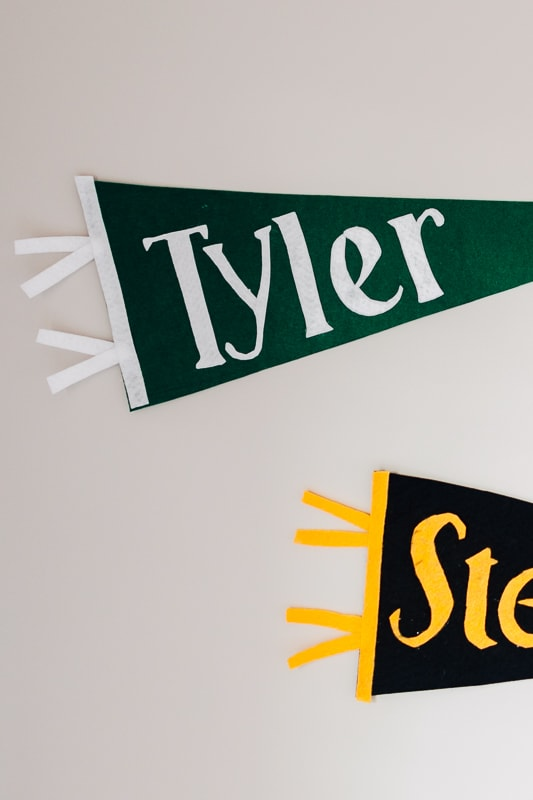 two diy felt pennants hanging on the wall in a bedroom.