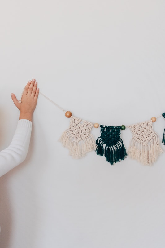 green and white diy macrame banner hanging on a wall