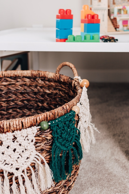 macrame banner in green and white with beads hanging from a basket