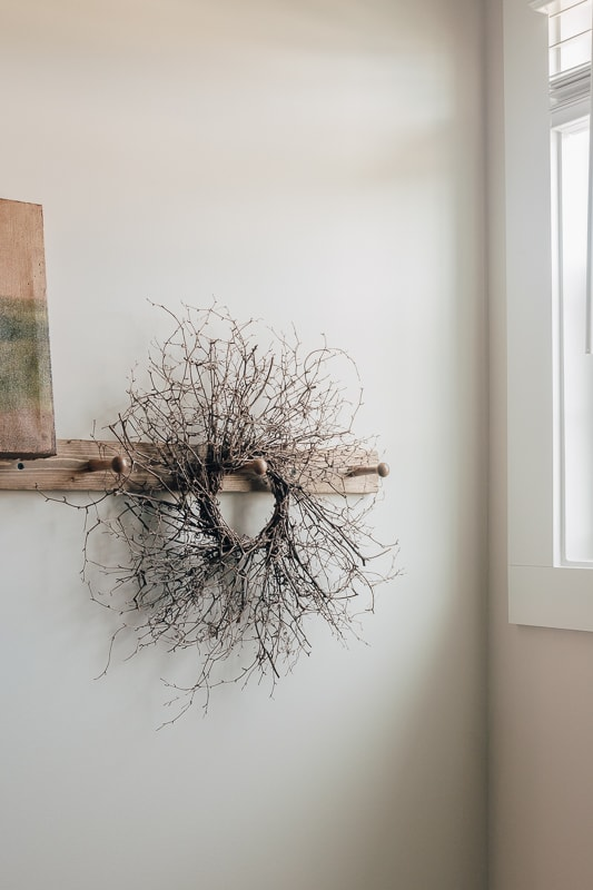 a grapevine wreath hanging from a peg rail with a light coming in from a nearby window