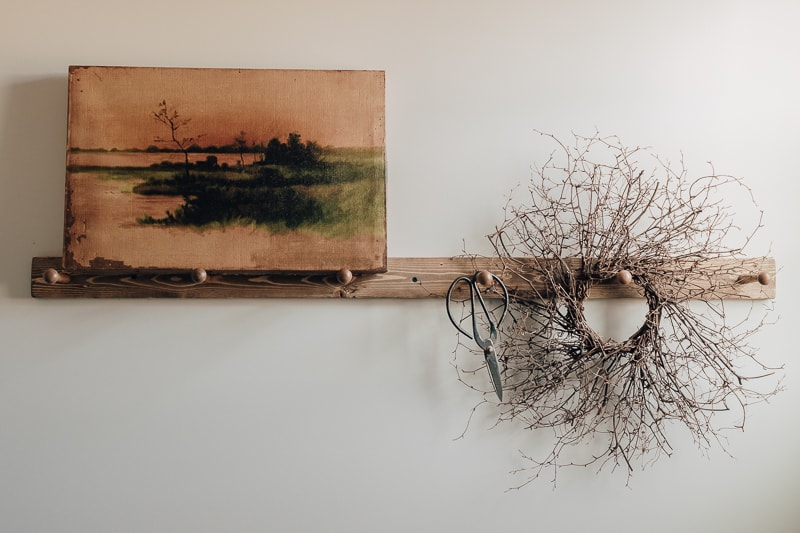 shaker style peg rail with a wreath and an old picture hanging on the wall