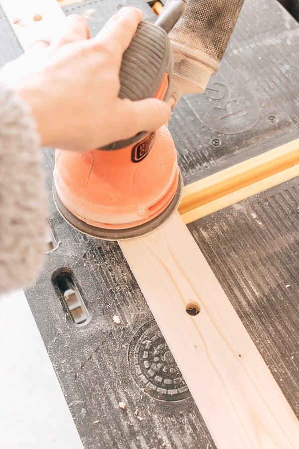 diy peg rail: sand your peg rail until smooth