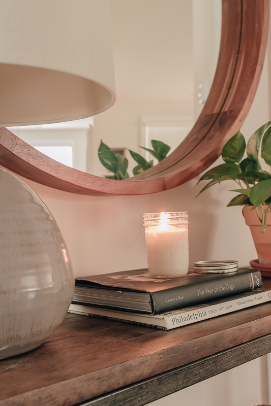 candle burning on top of books, with a lamp and a pothos plant in a terracotta planter. On a console table