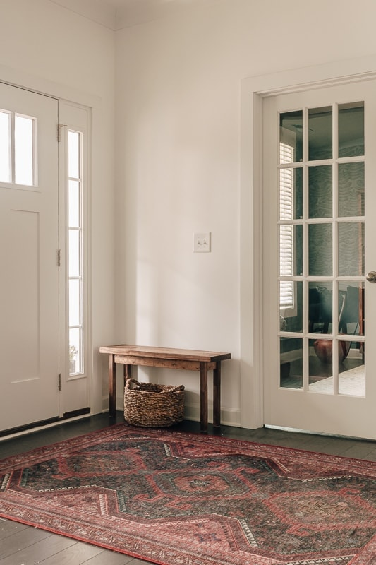 foyer with french door, red rug and wood bench. There is a basket underneath the wood bench.
