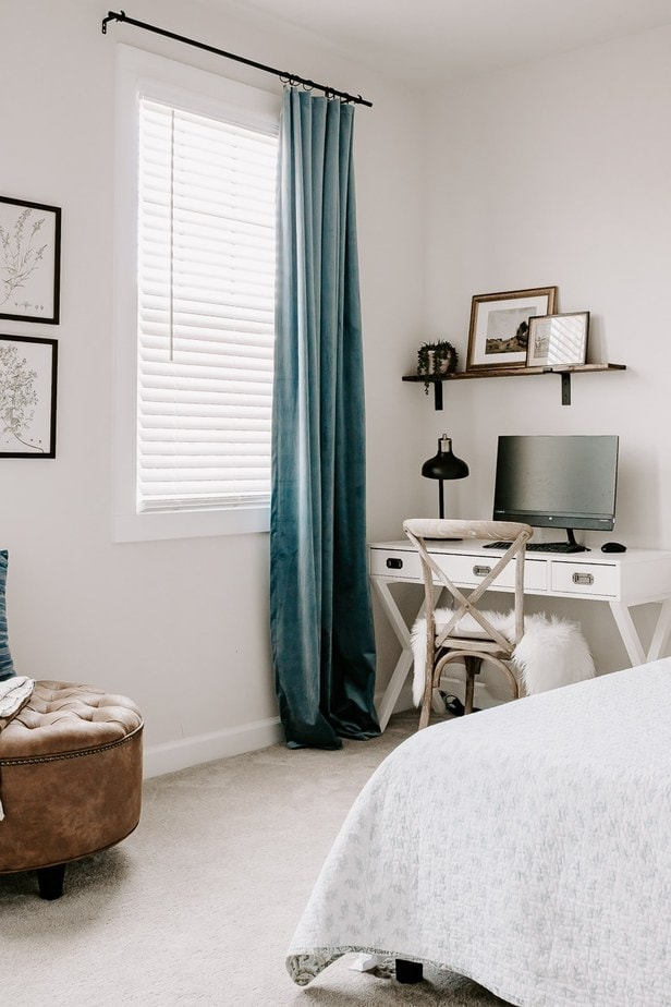 velvet blue drapes hanging in a bedroom next to a white desk. DIY Conduit curtain rods - full tutorial in the post!