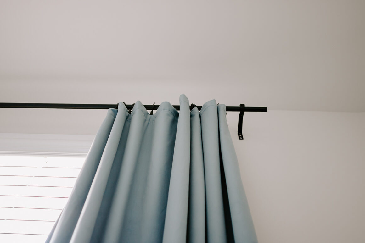 blue drapes hanging from Conduit Curtain Rods - how to make them yourself. Full tutorial in post!