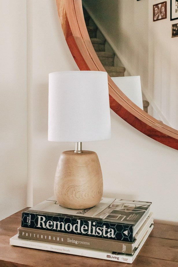 small brown accent lamp from Target on a stack of books in front of a mirror