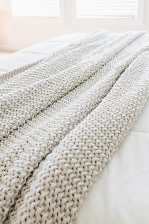 gray knitted bed blanket from Target on a bed with white bedding.