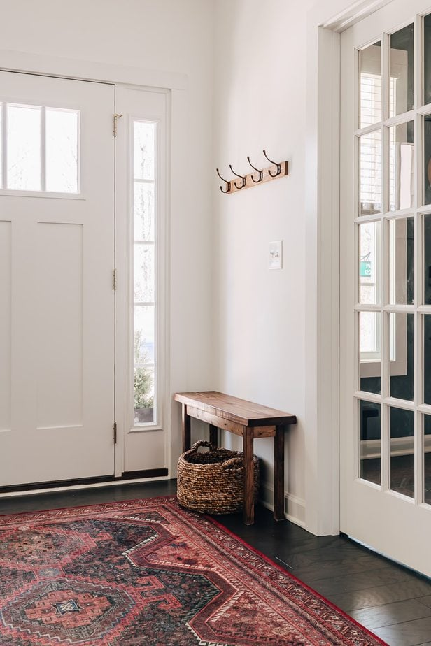 entryway with a red rug, a bench and farmhouse coat rack