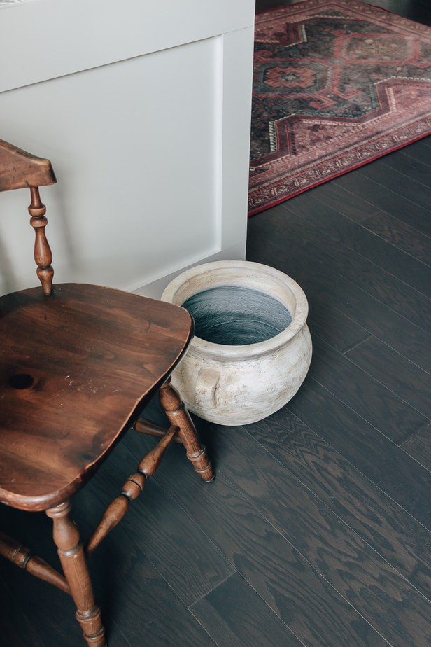 pot on the floor next to an old chair