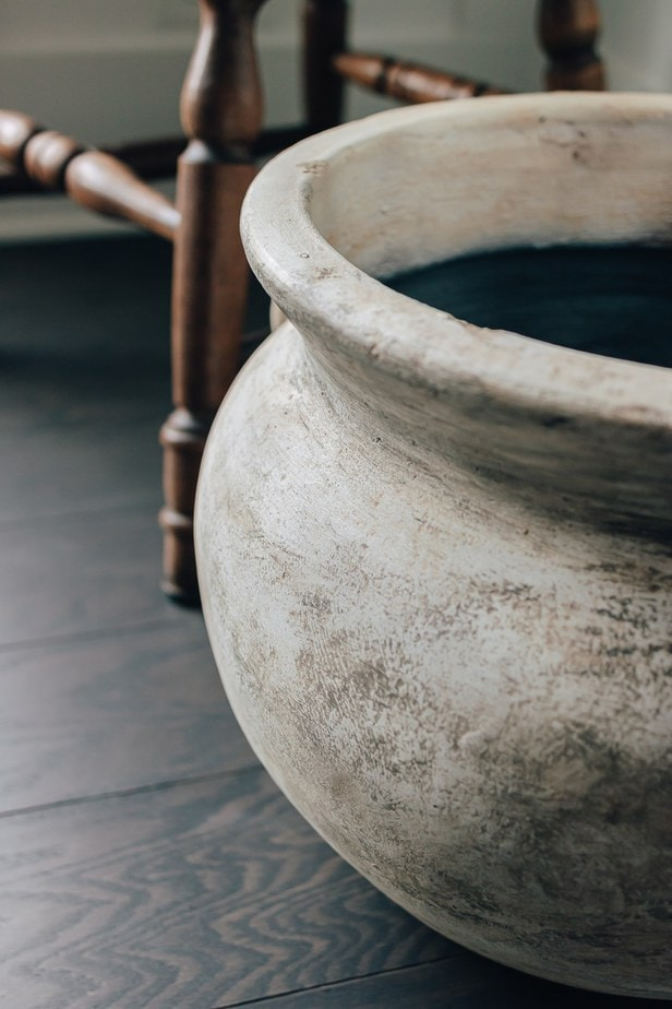 close up of an old jug vase, sitting on the floor next to a brown wood chair