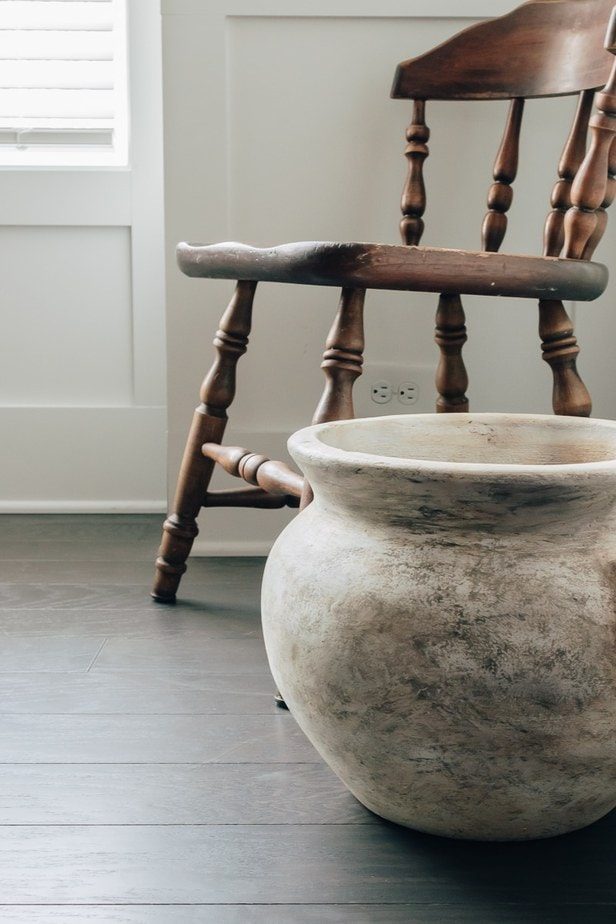 close up of an old jug, sitting on the floor next to a brown wood chairfind out how to turn any vase into a old relic