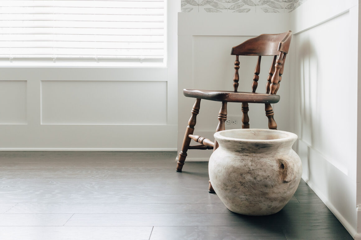 close up of an old jug, sitting on the floor next to a brown wood chairhow to make a vase look old - simple project!