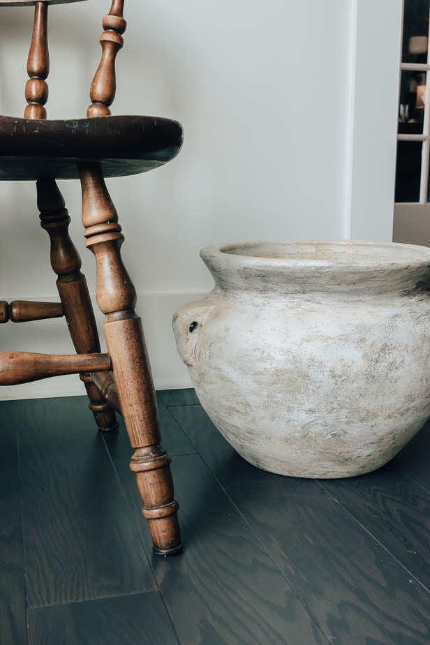 an old wood chair and a large, jug vase sitting on the floor next to it.