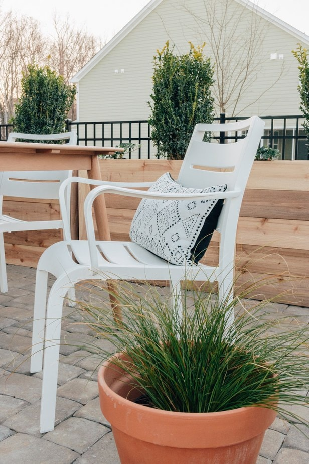 white outdoor chair with a black and white pillow on it and a green plant in the corner