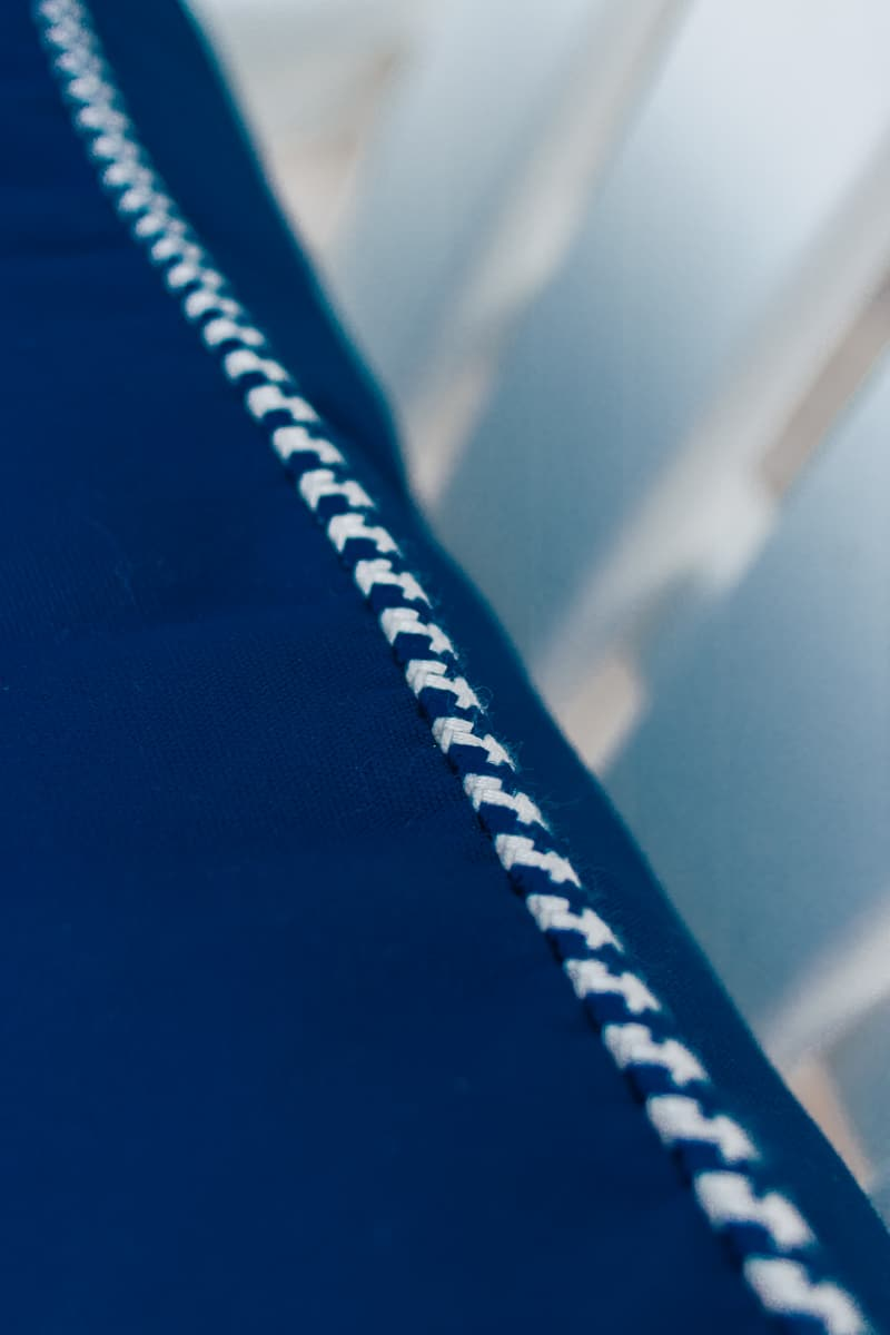close up view of a blue pillow with blue and white piping detail