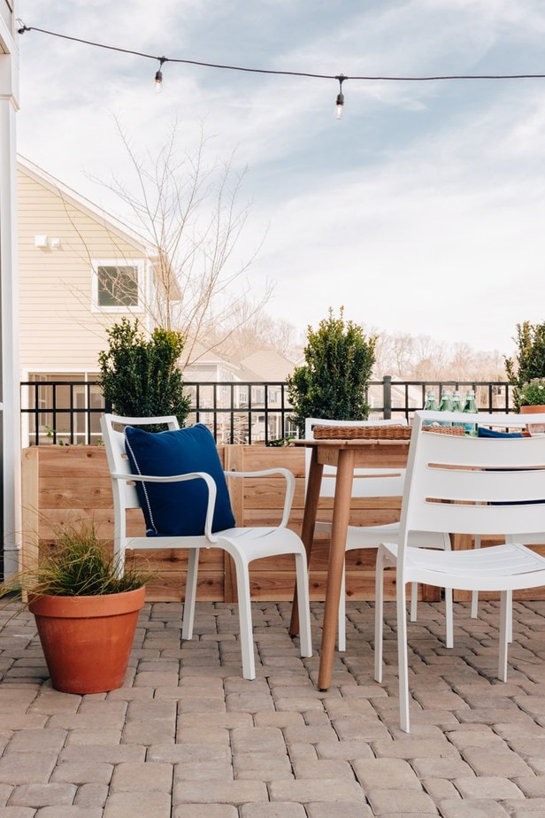 Outdoor dining set with blue pillows and a potted green plant