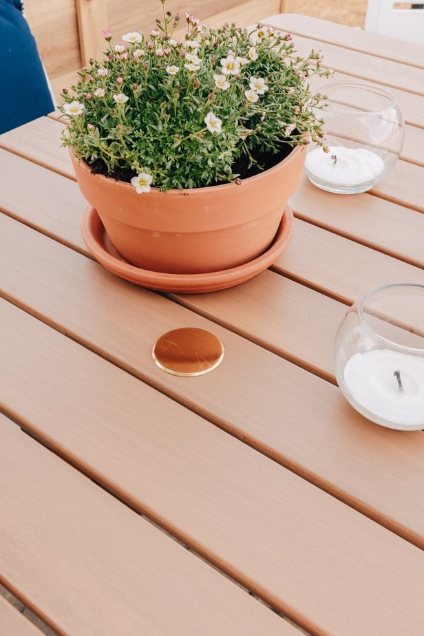 Close up of a brown wood outdoor table with a terracotta flower pot on it