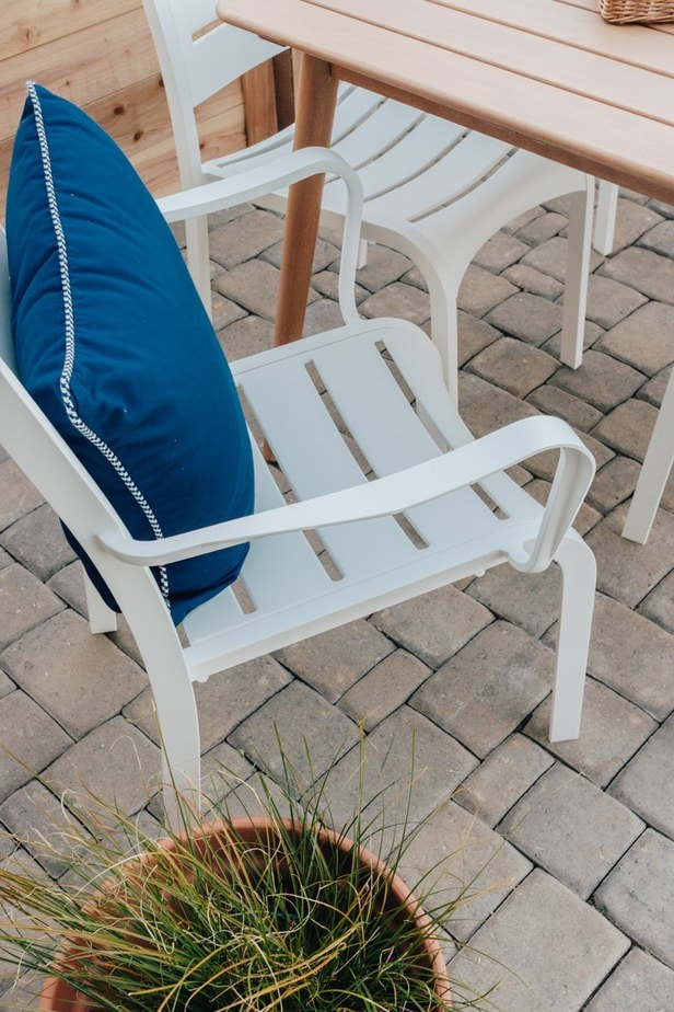 close up view of a white outdoor dining chair with a blue pillow on it