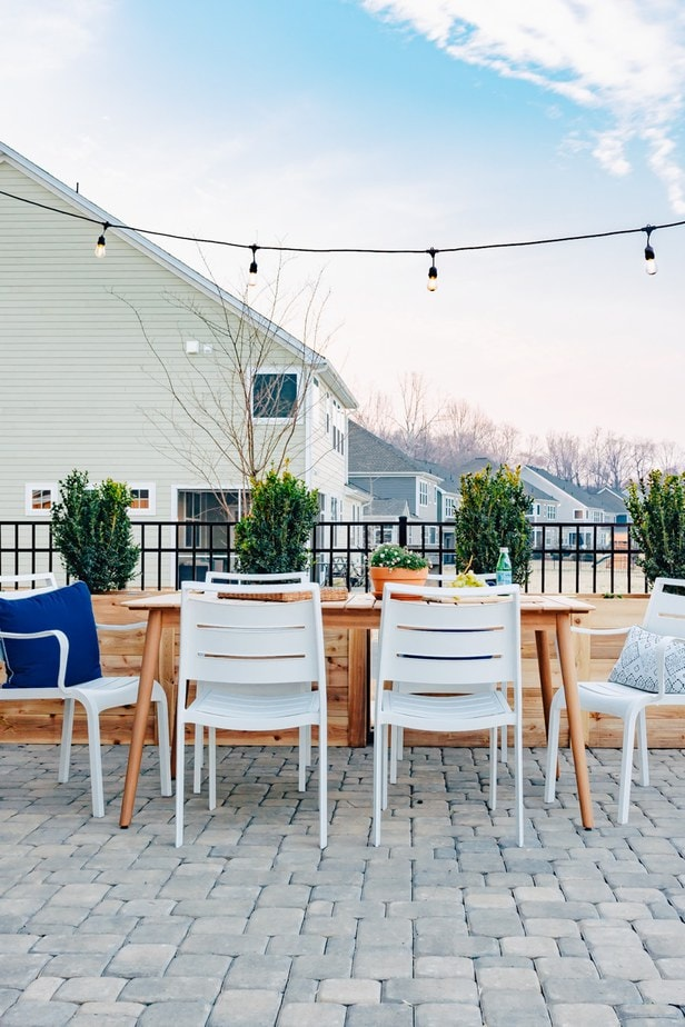 Eucalyptus outdoor dining table with white chairs. There are cafe lights hanging above. A dog is in the picture and a firepit in the corner