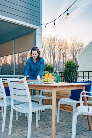 A woman in a blue shirt setting a tray down on an outdoor table