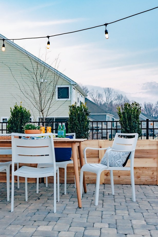 Eucalyptus outdoor dining table with white chairs. There are cafe lights hanging above