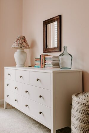 Girls room with a wood mirror and books and an old thrifted lamp.