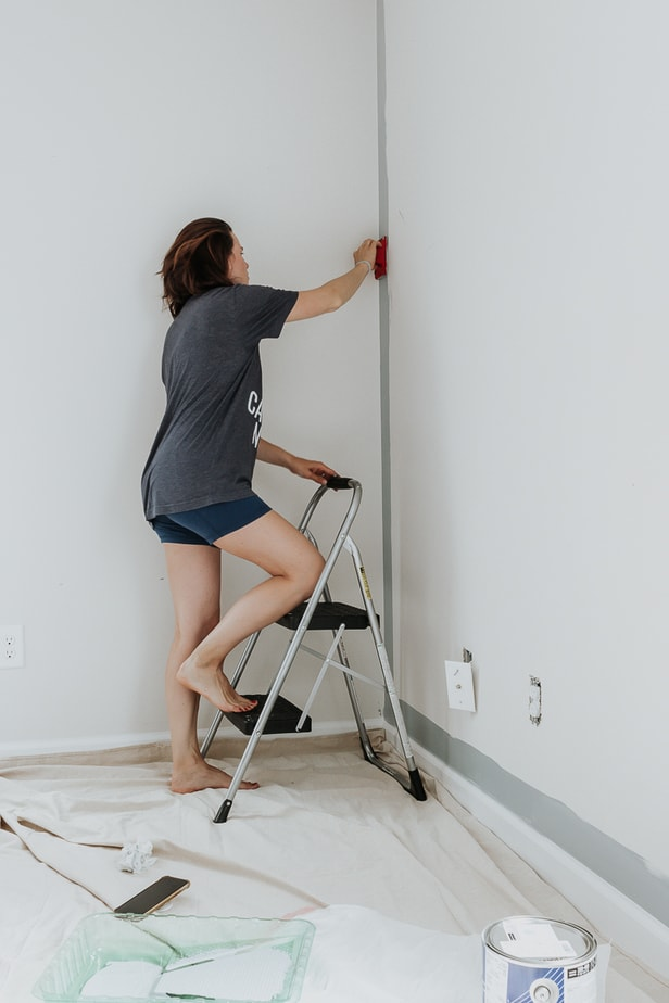 a woman using a paint edger on the wall