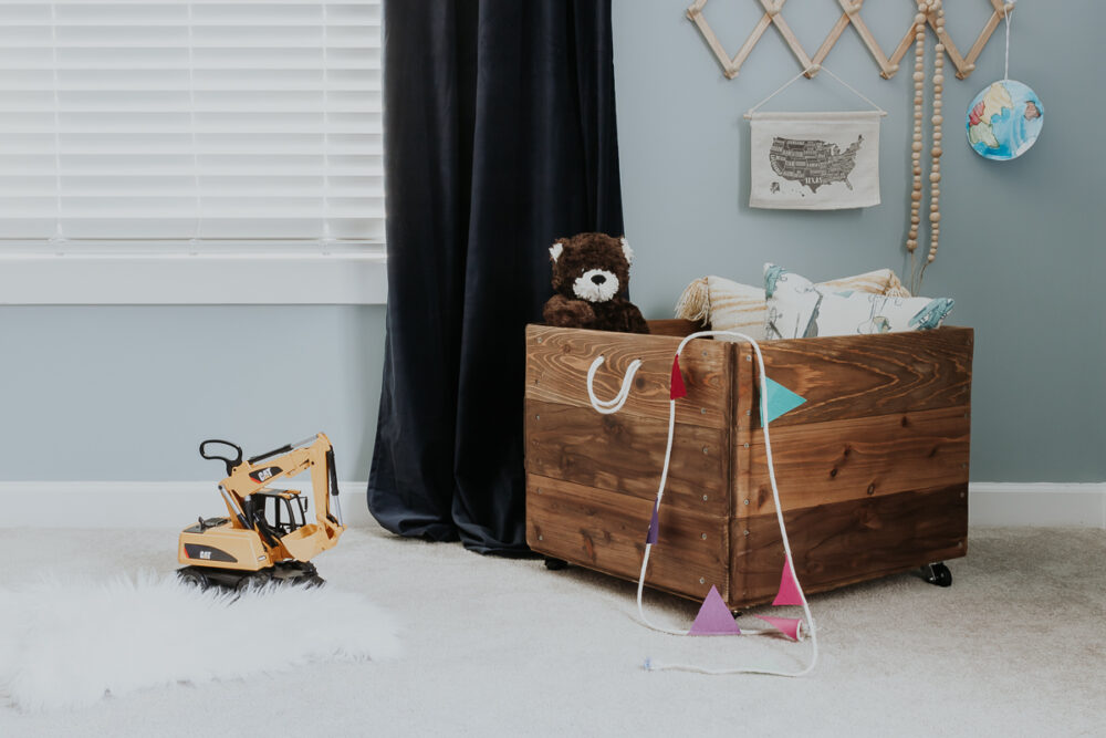 kids wood toy box on wheels with rope handles in a playroom - make this easy diy toy box