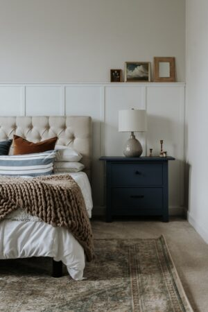 White painted board and batten wall with shelf in a bedroom