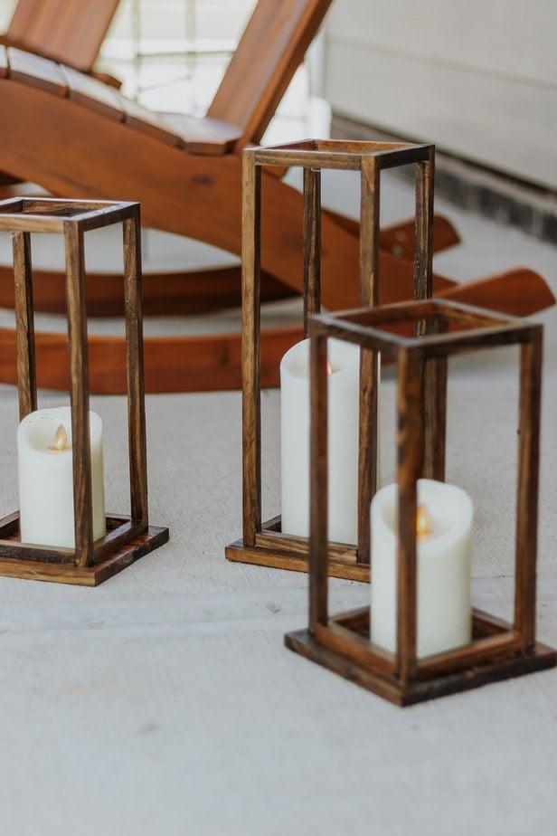 a set of three DIy Wood Lanterns on a front porch