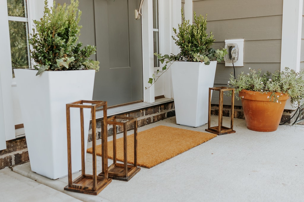 white painted outdoor planters with greenery in them and wood lanterns