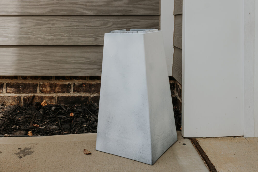 white plastic planter pot being spray painted - how to paint outdoor planters - full tutorial in post