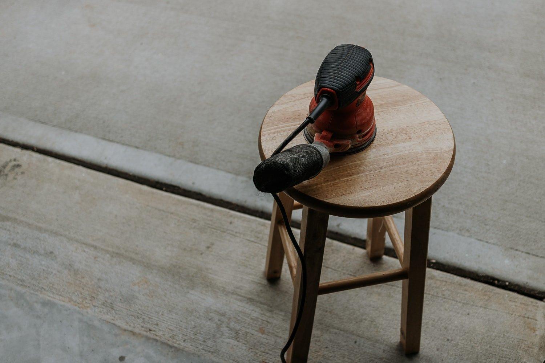 sanding a bar stool with an orbital sander