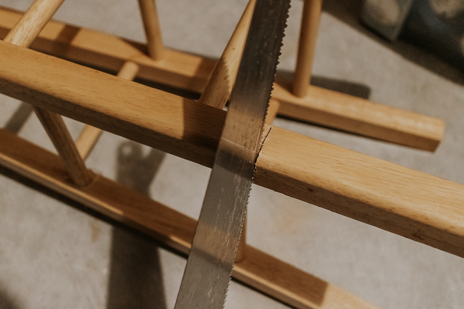 sawing the legs off a bar stool to make a side table